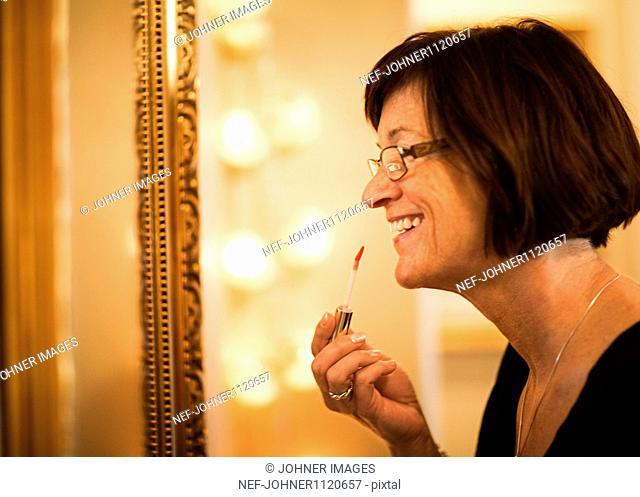 Mature woman applying lipstick, smiling