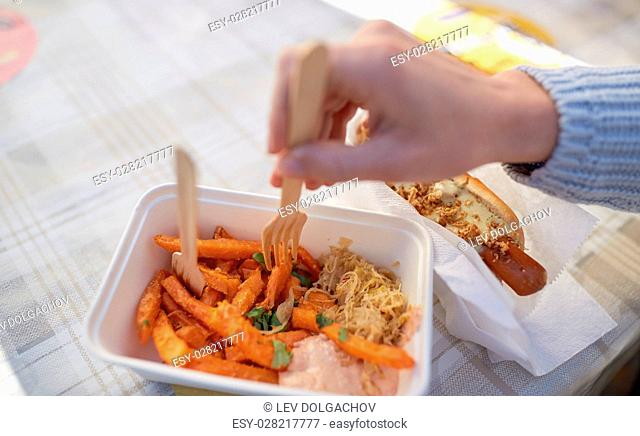 fast food, people and unhealthy eating concept - close up of hand with hot dog and sweet potato in disposable plate outdoors