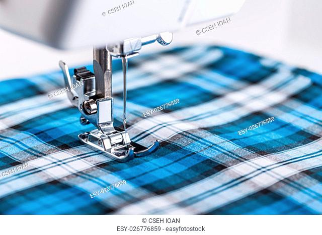 Part of sewing machine and checkered fabric closeup
