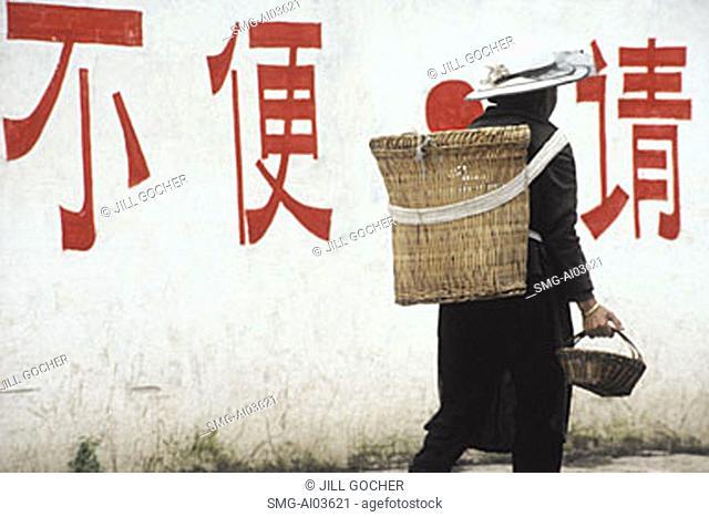 China, Lijiang, Naxi person carrying basket