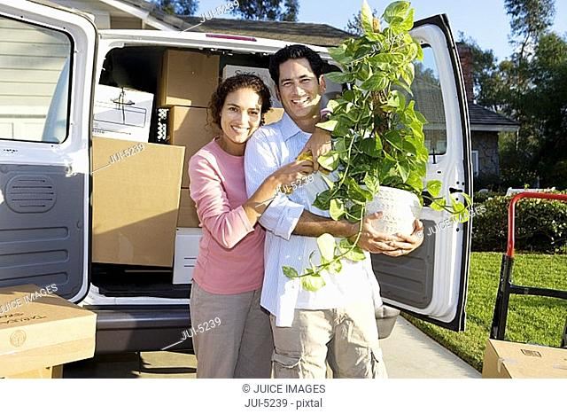 Couple moving house, standing beside van in driveway, man holding pot plant, smiling, portrait