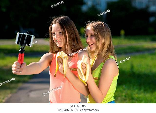 Two girls girlfriend, in a park in nature. In the hands holding bananas. Records video on the smartphone. Emotions of joy and pleasure