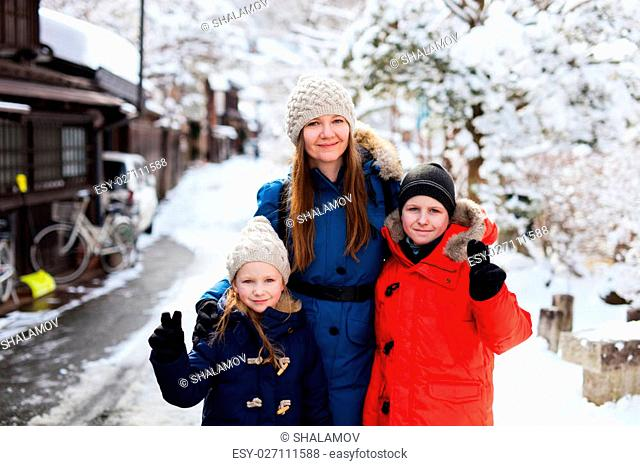 Family of mother and kids at old district of historical Takayama town in Japan on winter day