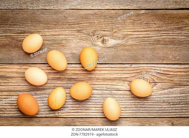 brown chicken eggs on a rustic weathered wooden table, top view with a copy space