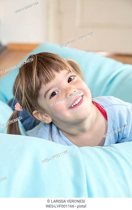 Portrait of smiling little girl lying on bean bag