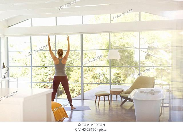 Woman practicing yoga mountain pose in luxury hotel bedroom