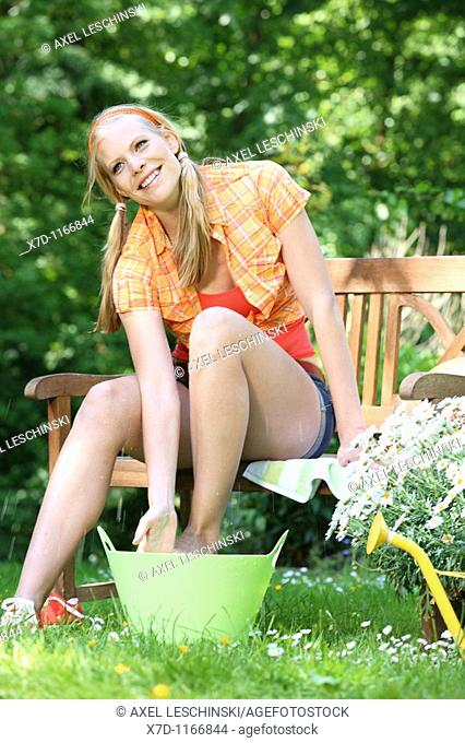Young blond woman cooling her legs with cold water sitting in the garden
