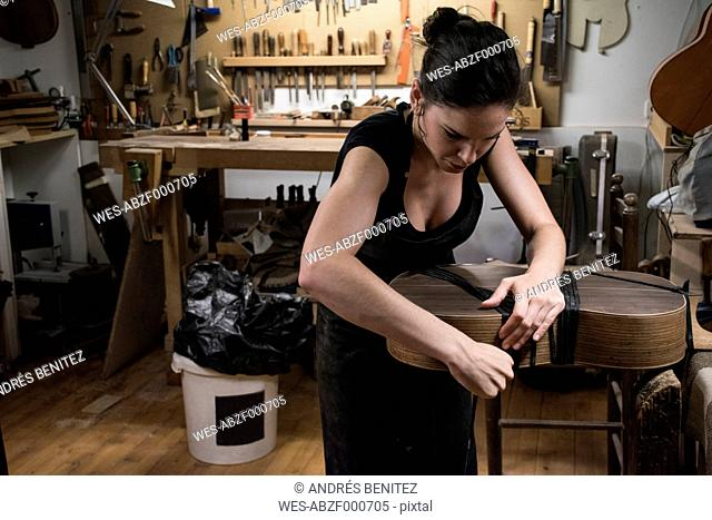 Luthier manufacturing a guitar in her workshop