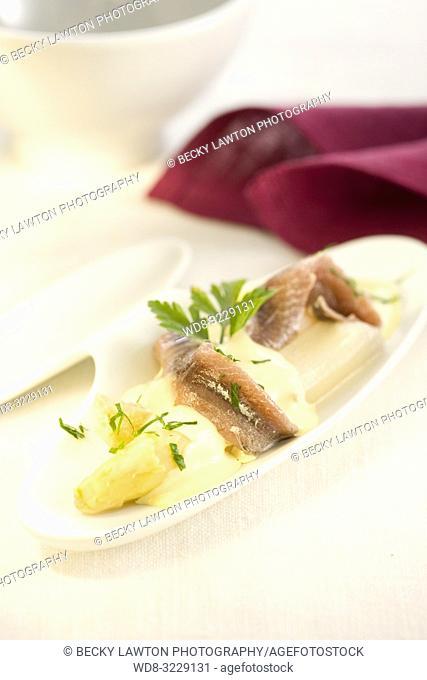 Platillo de esparragos blancos y filetes de anchoas con salsa de mantequilla