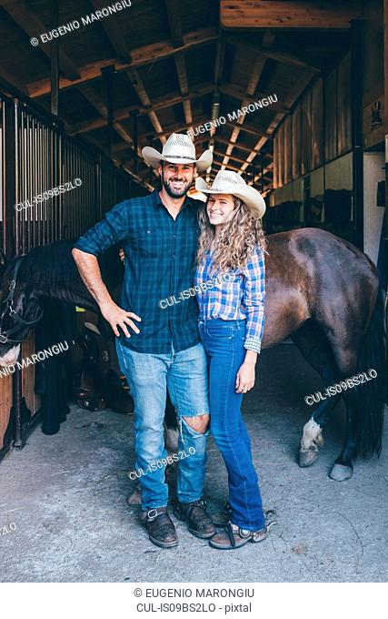 Young cowgirl and boyfriend at stable entrance, portrait