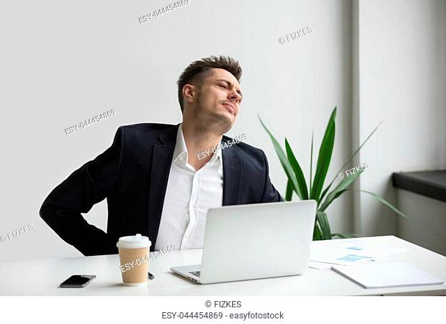 Upset businessman touching aching back feeling strong backache pain in tensed muscles sitting on uncomfortable office chair at work