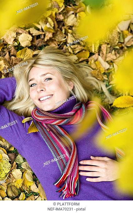 A woman resting on autumn leaves Sweden