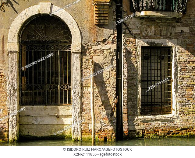 Architectonical detail of an old door and window. Venice. Veneto. Italy