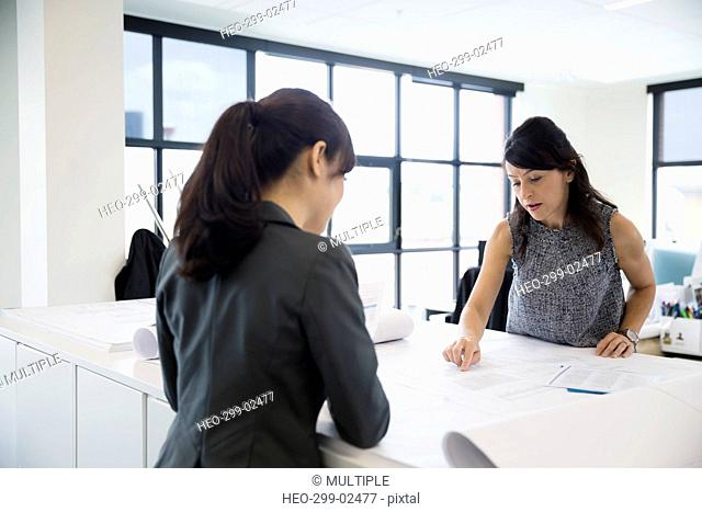 Female architects reviewing paperwork in office