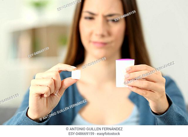 Confused woman doubting between saccharine and sugar at home