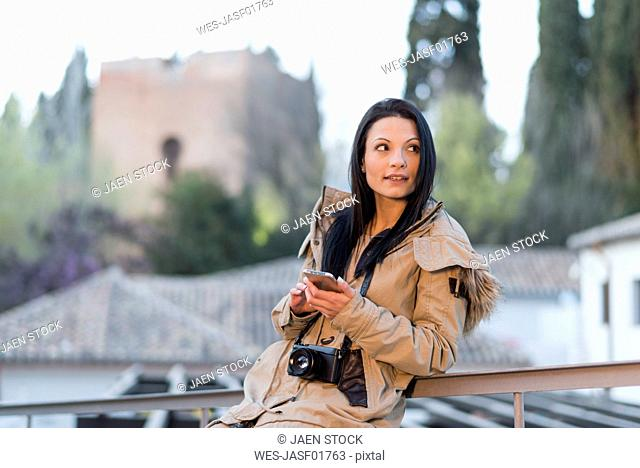 Spain, Granada, young woman with camera and cell phone in front of the Alhambra