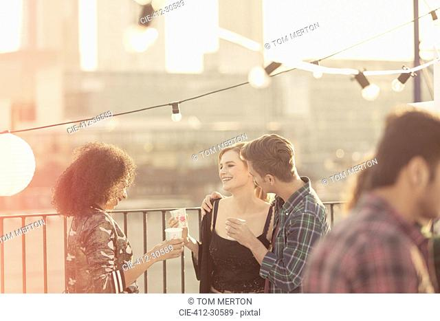 Young adult friends talking and drinking at rooftop party