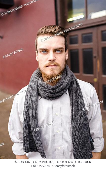 Hipster posing outdoors for the camera with a fashion forward style and a modern man appearance