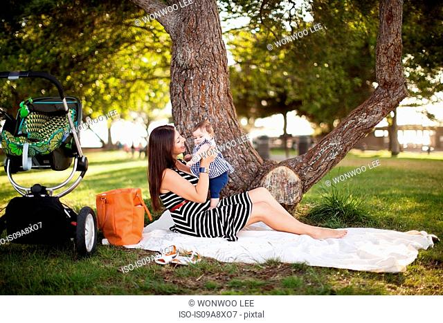 Mother sitting on picnic blanket with baby daughter