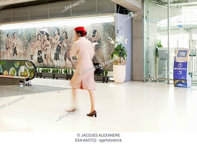 Blurred motion of air hostess using cell phone at Bangkok international airport