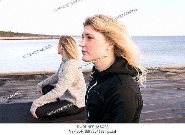 Two women sitting on pier