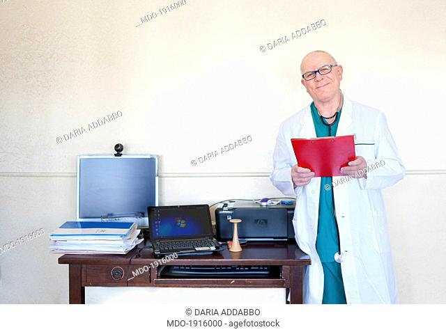 An obstetrician beside a desk covered with computers and files. Palermo (Italy), March 2014