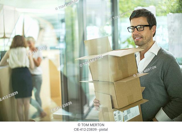 Businessman carrying cardboard boxes in office