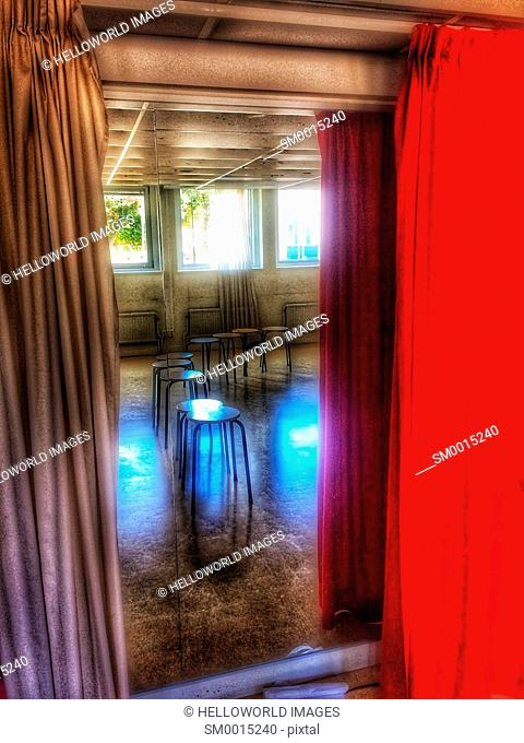 Row of empty stools reflected in mirror between curtains