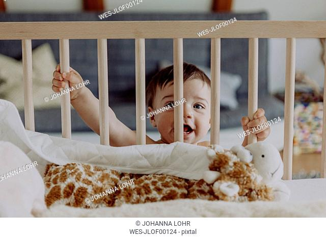 Baby boy holding on to his cot laughing