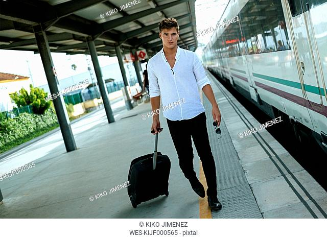 Young man with suitcase walking at station platform