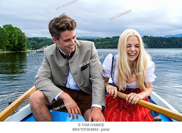 Germany, Bavaria, young couple wearing traditional clothes sitting in a rowing boat on Staffelsee