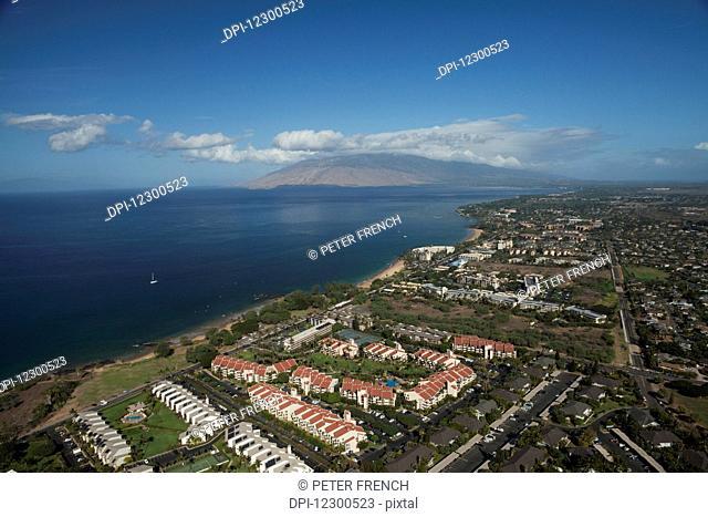 Aerial view of condominiums, Kihei and Wailea, a sailboat and the West Maui mountains; Kihei, Maui, Hawaii, United States of America