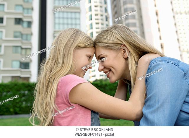 Happy mother and daughter smiling at each other urban city garden