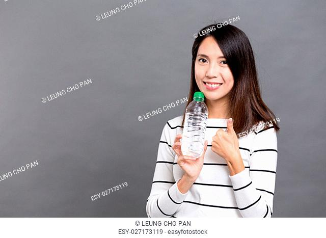 Woman holding water bottle and showing thumb up