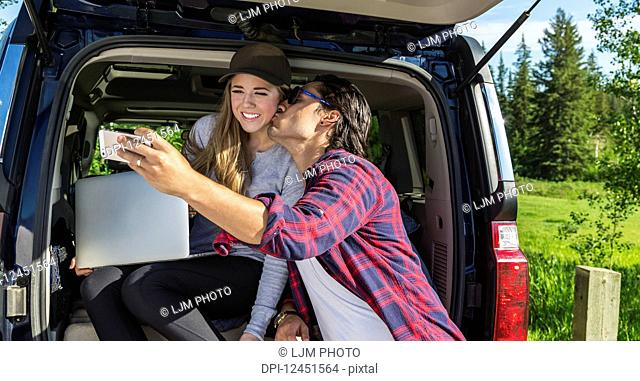 Young couple at their vehicle with the back open looking at a laptop computer and taking a self-portrait with a smart phone; Edmonton, Alberta, Canada