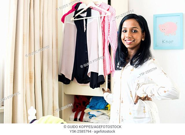 Tilburg, Netherlands. Young, dark skinned woman cleaning up her wardrobe closet in her bedroom