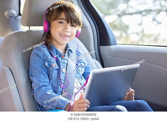 Portrait of smiling girl with headphones using digital tablet in back seat of car
