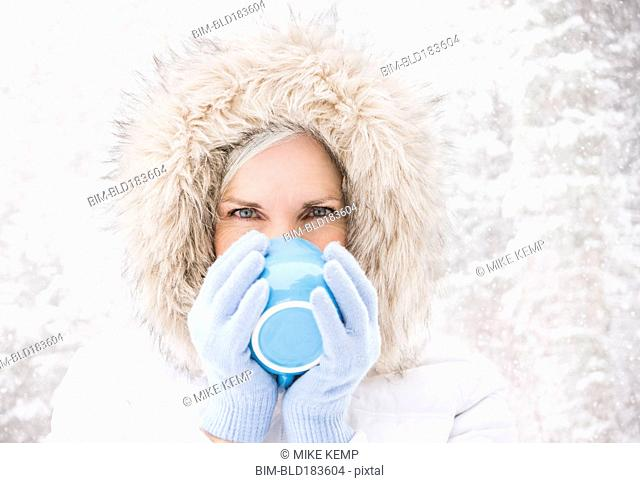 Caucasian woman drinking coffee in snow