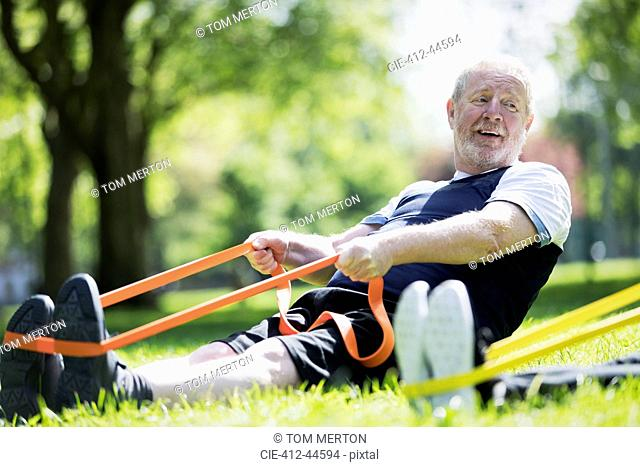 Active senior man exercising in park, stretching with resistance band