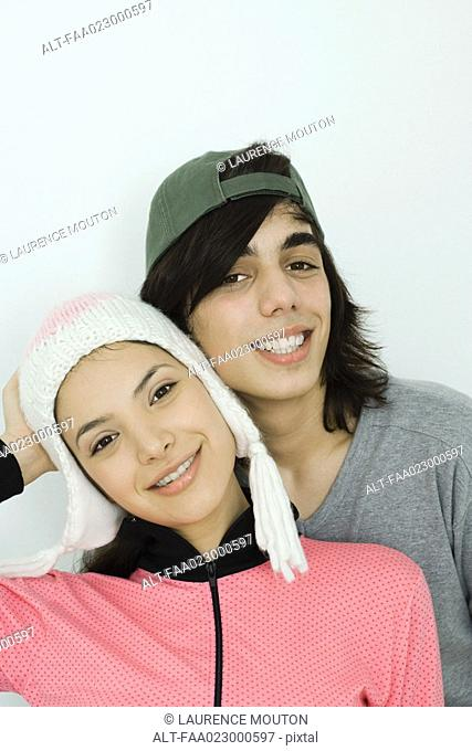 Young couple smiling at camera together, both wearing hats, cheek to cheek, portrait