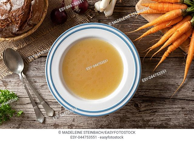 Chicken bone broth with fresh vegetables, top view