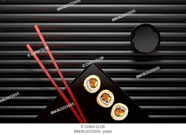 Chopsticks and sushi on square plate with dipping sauce