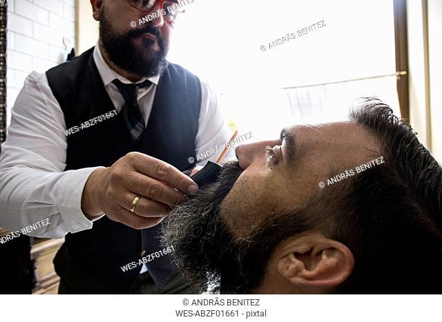 Barber cutting man's beard