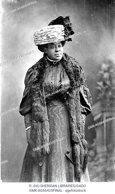 Portrait of an African American woman standing, wearing a hat and fur stole, 1915