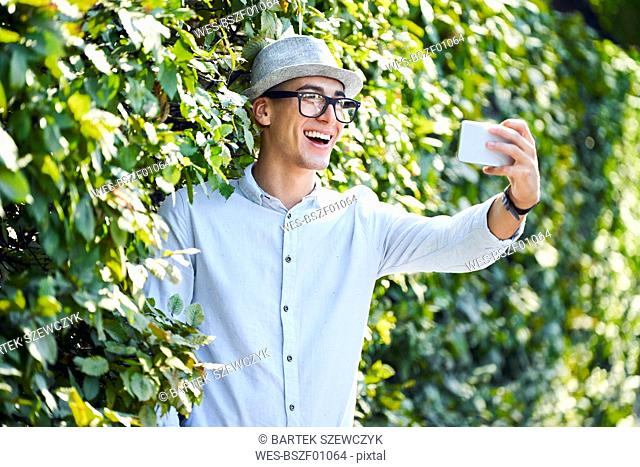 Happy young man taking selfie in a hedge