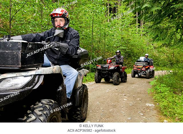A group of adult men on their ATV quad bikes ride the trails near Powell river on the upper Sunshine coast, Vancouver coast and mountain range, British Columbia