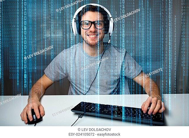 technology, gaming, entertainment, let's play and people concept - happy smiling young man in eyeglasses with headset playing computer game at home and...