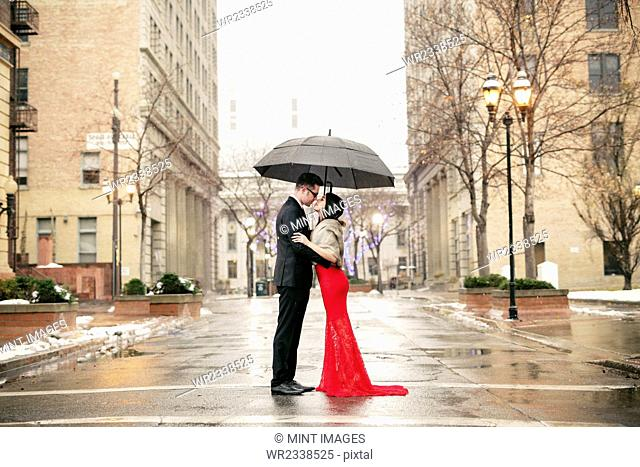 A woman in a long red evening dress with fishtail skirt and a fur stole, and a man in a suit, kissing under an umbrella in the city