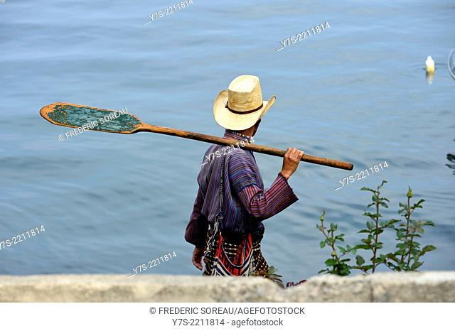 Man with traditional clothing carrying paddle in Lake Atitlan in Guatemala, Central America