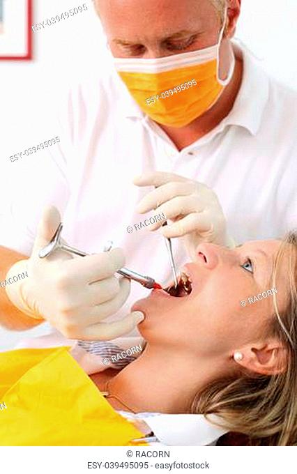 Male dentist wearing mask injecting woman's mouth in clinic